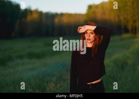 Spain, Andalusia, Granada. Beautiful red-haired woman looking at Sunset in nature. Lifestyle concept. - Stock Photo