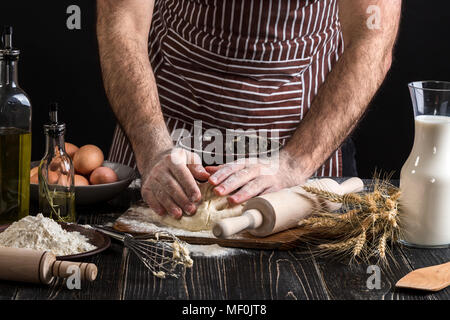 Against the background of men's hands knead the dough. Ingredients for cooking flour products or dough bread, muffins, pie, pizza dough . - Stock Photo