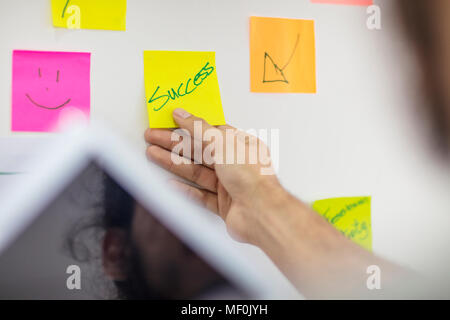 Hand putting a sticky note on board - Stock Photo