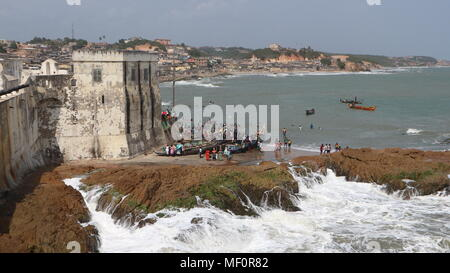 Fishing boats and people on the beach near the fort in Cape Coast, Ghana - Stock Photo