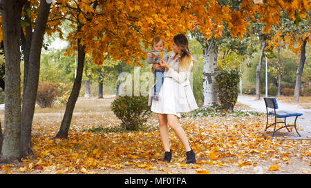Beautiful smiling mother giving yellow leaf from tree at park Stock Photo