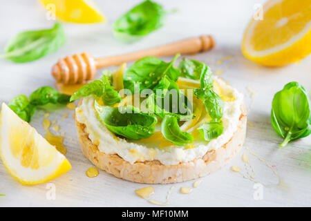 Healthy snack with crisp bread, lemon zest, honey and basil. Easy appetizer recipe. - Stock Photo