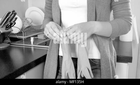 Black and white closeup photo of young housewife wearing rubber gloves - Stock Photo
