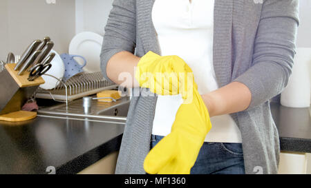 Closeup photo of young housewife with yellow latex gloves - Stock Photo