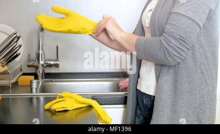 Closeup photo of young housewife in yellow protective gloves on kitchen - Stock Photo