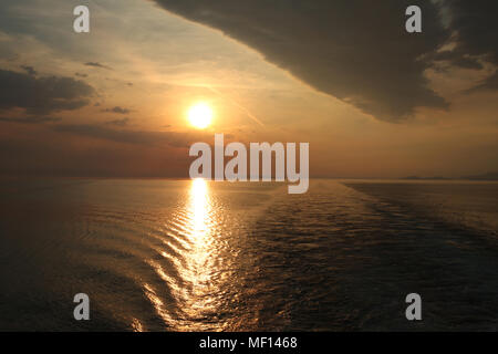 Golden sunset over the ocean with a beautiful reflection in the sea. - Stock Photo