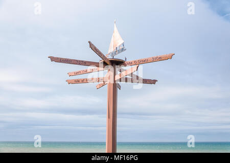 Tourist direction & distance signs mounted on post with weather vane on top, located on shorefront in Port William, Dumfries & Galloway, Scotland, UK - Stock Photo