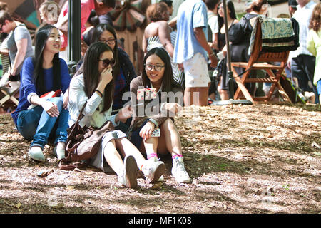 A group of Asian teenage girls laugh as they take a selfie with a selfie stick at the Atlanta Dogwood Festival on April 11, 2015 in Atlanta, GA. - Stock Photo
