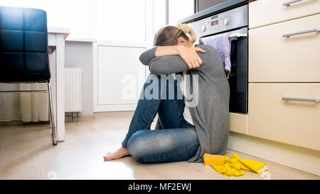 Young housewife in depression sitting on floor at kitchen - Stock Photo