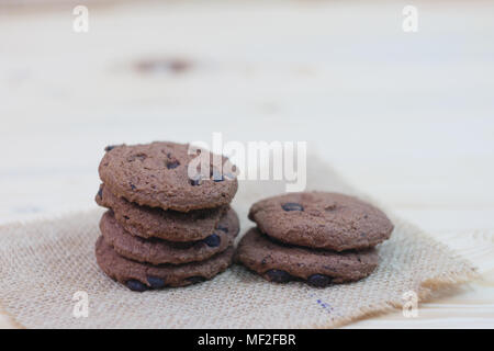 Chocolate chip cookies are placed on sackcloth on a wooden table. - Stock Photo