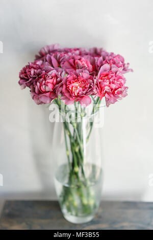 beautiful carnation flowers in a vase on a table . Bouquet of violet, purple and pink multicolor flower. Decoration of home. Wallpaper and background. - Stock Photo