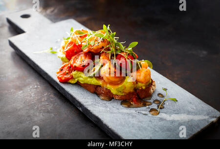 Crostini with shrimps and tomatoes, roasted bread, herbs, avocado cream, sweet chili sauce, jalapenos, cress - Stock Photo