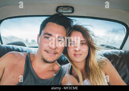 Cuba, Yound couple sitting in a vintage car, taking a selfie - Stock Photo