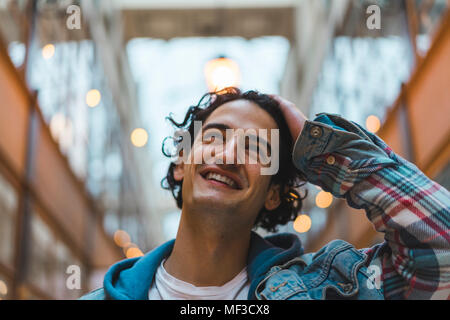 Portrait of smiling young man in shopping centre - Stock Photo