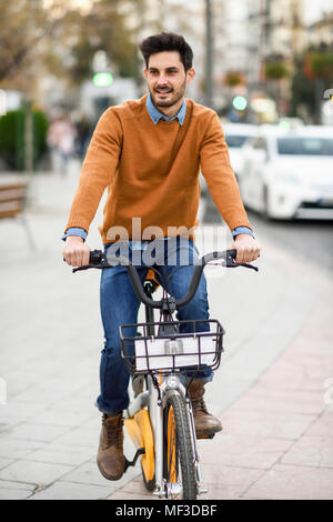 Spain, Andalusia, Granada. Handsome young man on shared bicycle in the city. Lifestyle concept. - Stock Photo