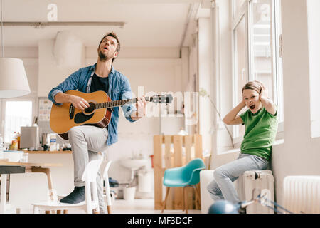 Horrified son covering his ears with father playing guitar at home - Stock Photo