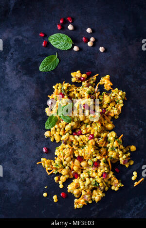 Couscous salad with chick peas and cranberries on dark ground - Stock Photo