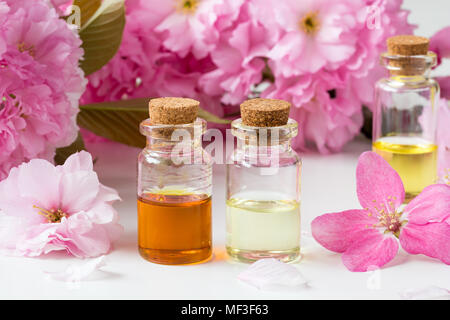 Bottles of essential oil with pink cherry blossoms on a white background - Stock Photo