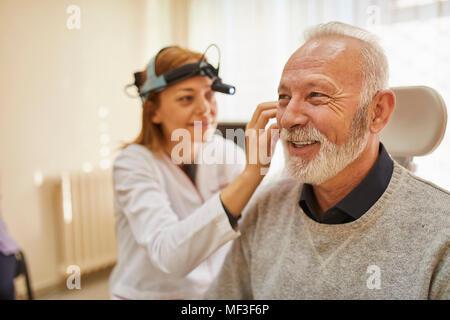ENT physician examining ear of a senior man - Stock Photo
