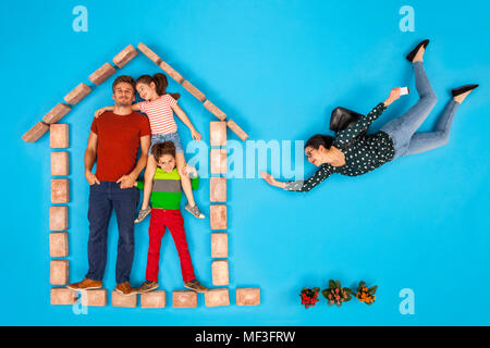 Father and children waiting at home, while mother is coming home from work - Stock Photo