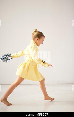 Laughing little girl running barefoot in front of light background