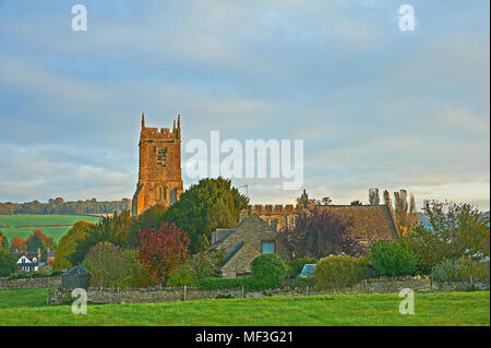 Rural South Warwickshire scene withSt Peter's church in the village of Long Compton with early morning sunshine lighting up the church tower - Stock Photo