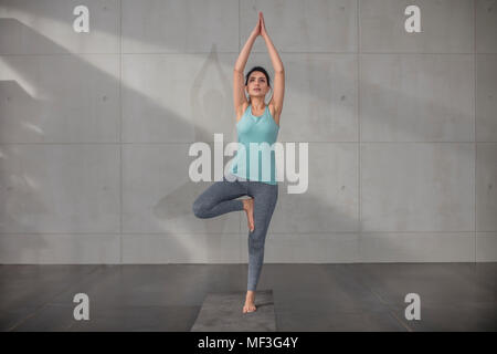 Young woman doing yoga exercise in studio - Stock Photo