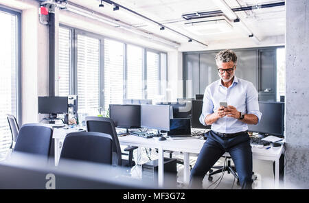 Smiling mature businessman sitting on desk in office using smartphone - Stock Photo