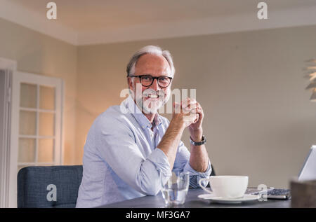 Portrait of happy mature man with laptop and cup of coffee sitting at table in his living room - Stock Photo