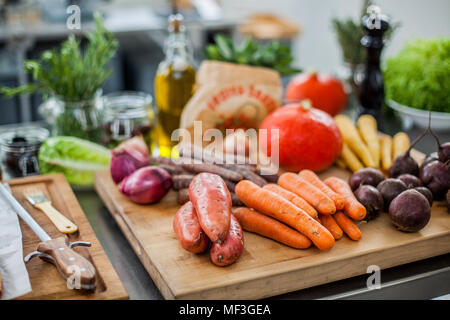 Different fresh vegetables on chopping board - Stock Photo
