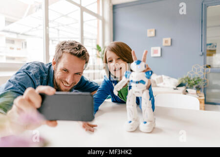 Happy father and son taking a selfie with robot on table at home