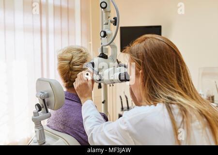 ENT physician examining ear of a senior woman - Stock Photo