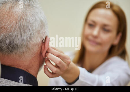 Female doctor applying hearing aid to senior man's ear - Stock Photo