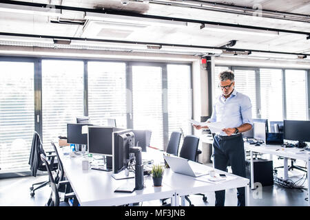 Mature businessman standing in office reading documents - Stock Photo