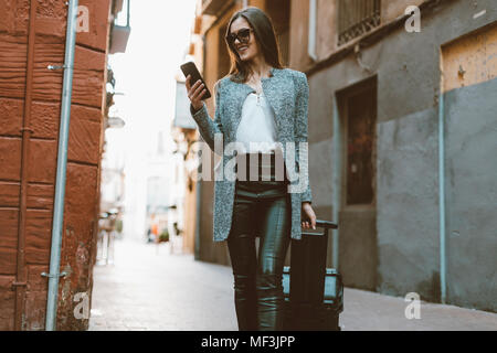 Young businesswoman in the city checking cell phone - Stock Photo