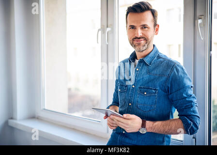 Portrait of smiling man holding tablet at the window - Stock Photo
