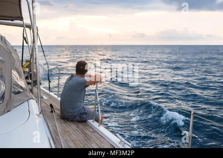 Indonesia, Lombok island, man sitting on deck of a sailing boat - Stock Photo