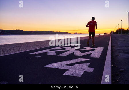 Portugal, Lisbon, Tagus river at sunset, jogger - Stock Photo