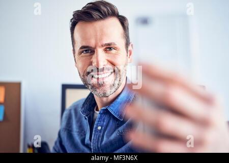 Happy man in office taking selfie - Stock Photo
