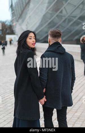France, Paris, portrait of young woman hand in hand with her boyfriend - Stock Photo