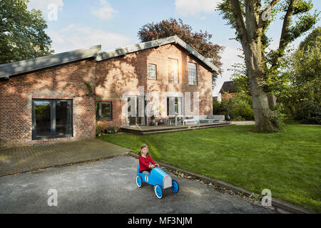 Girl playing with soapbox in driveway of residential house - Stock Photo