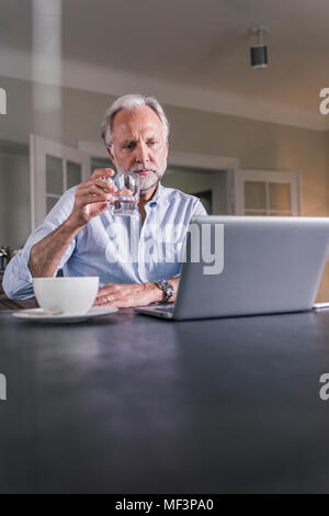 Pensive mature man sitting at table with glass of water looking at laptop - Stock Photo