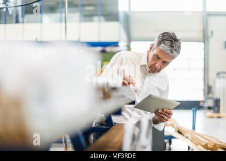 Businessman using tablet in production hall - Stock Photo