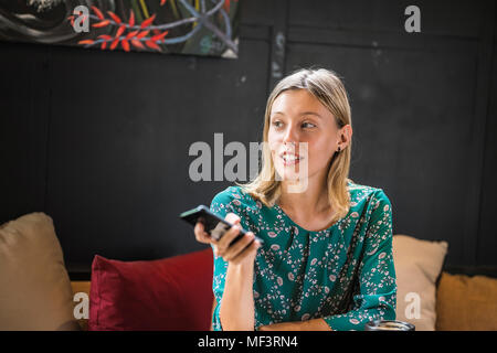 Young smiling woman with green dress sitting in cafe,  holding her smartphone - Stock Photo