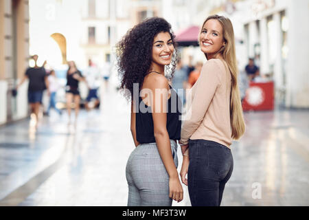 Portrait of two happy friends on the street - Stock Photo
