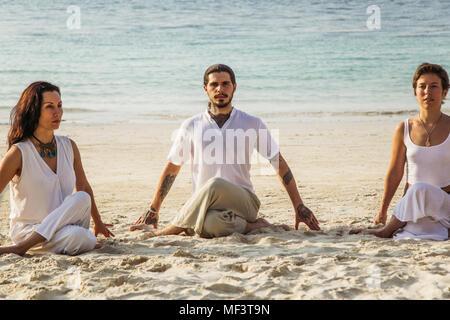 Thailand, Koh Phangan, three people doing yoga on a beach - Stock Photo