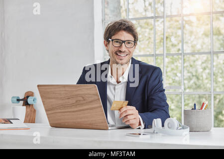 Portrait of smiling businessman with laptop on desk holding credit card - Stock Photo