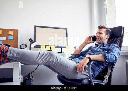 Relaxed man sitting at desk in office talking on cell phone - Stock Photo
