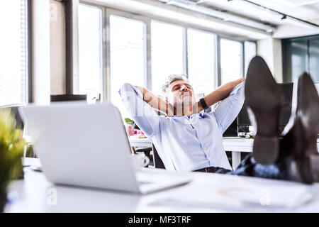Relaxed mature businessman sitting at desk in office leaning back - Stock Photo