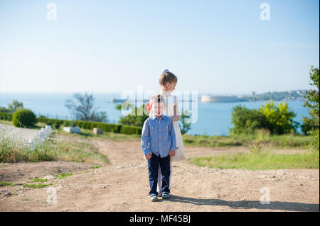 two happy beautiful kids standing near sea coast smiling back to back - Stock Photo